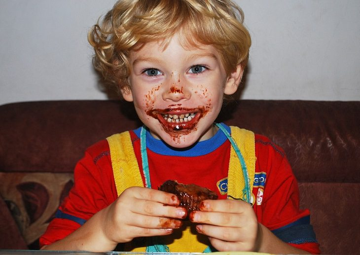 יום הולדת בריא: ילד מרוח בשוקולד אוכל עוגה ומחייך
