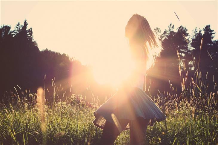 כל מה שצריך לדעת על ספיגת ויטמין D מהשמש: אישה בשדה מול אור השמש
