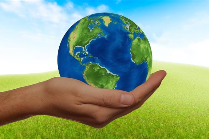 בחן את עצמך: יד מחזיקה את כדור הארץ על רקע דשא
