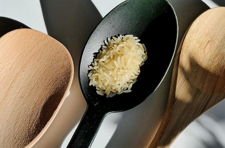 טיפים להכנת אורז: כפות עץ וכף אחת עם אורז לא מבושל