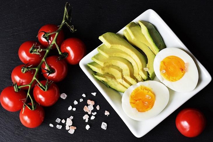 שילובי מזון להרזיה: ביצה קשה פרוסה ואבוקדו פרוס בצלחת ולידם עגבניות
