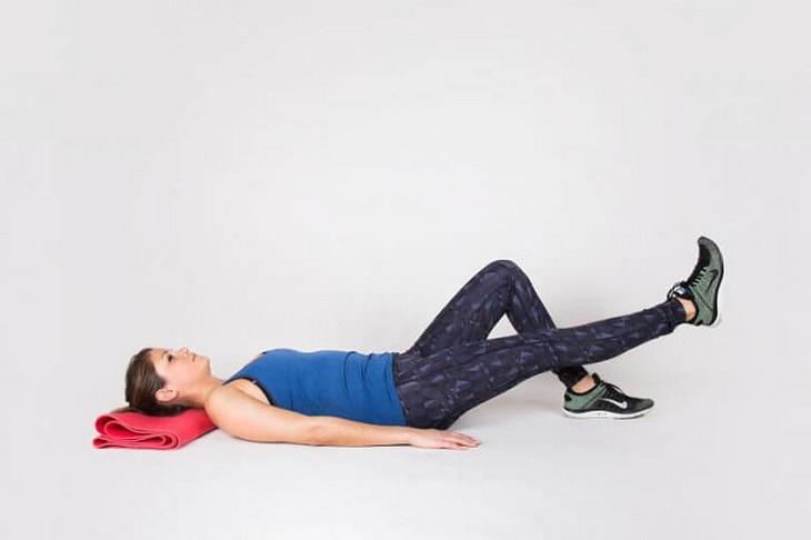 תרגילים לכאבי ברכיים: אישה מדגימה תרגיל מתיחה הרמה ישרה של הרגל