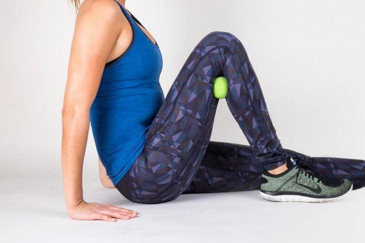 תרגילים לכאבי ברכיים: אישה מדגימה תרגיל מתיחה כדור מתחת לברך