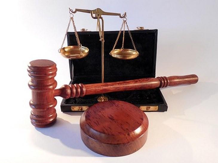 לבנות אמון מחדש: מאזניים ממתכת עם פטיש של שופט ובסיס עץ