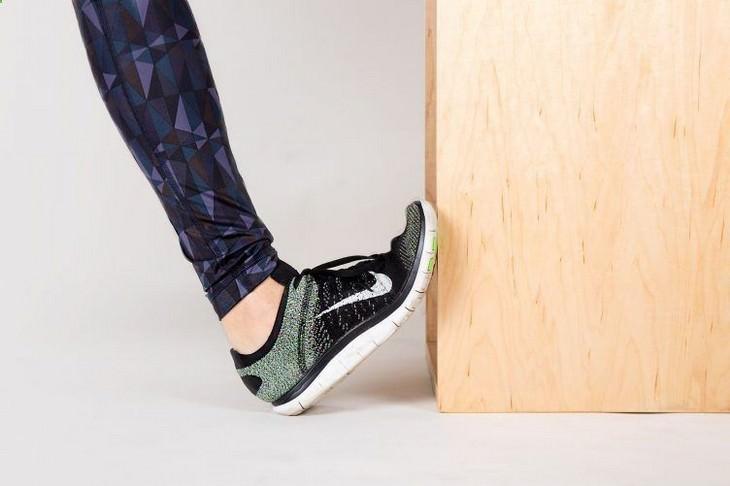 תרגילים לכאבי ברכיים: אישה מדגימה תרגיל מתיחה רגל מול קיר