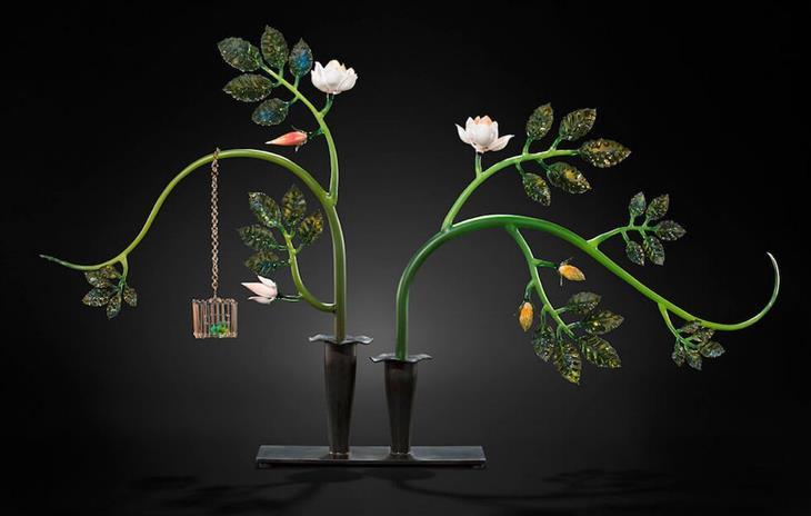 יצירות מזכוכית: זוג פמוטים ומתוכם יוצאים שני גבעולים עם פרחים ועלים