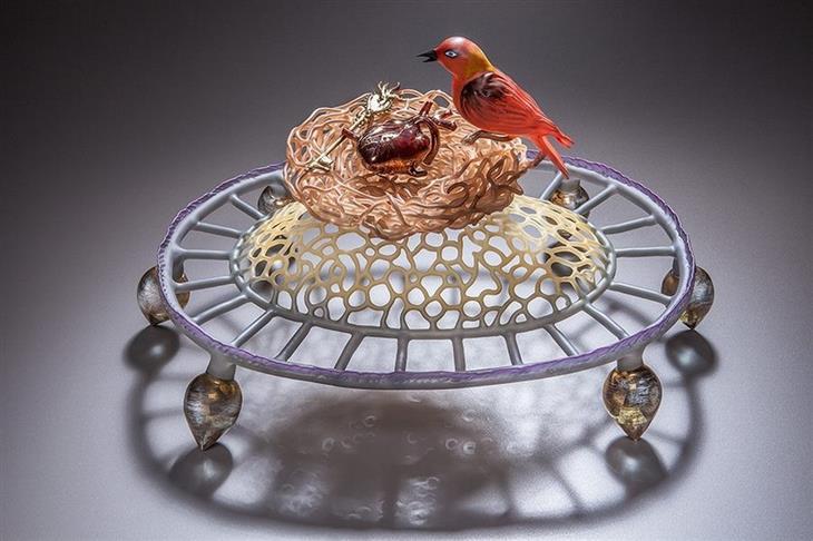 יצירות מזכוכית: ציפור אדומה עומדת על קצה הקן שלה שבתוכו סיכת זהב