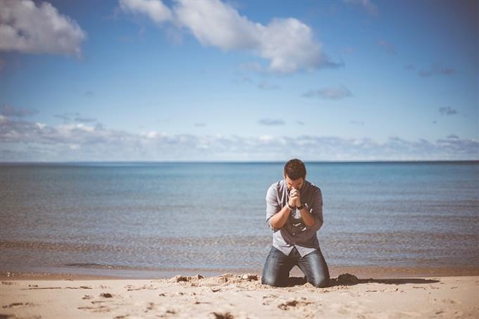 שאלון אישיות נבחרת במונדיאל: אדם כורע על ברכיו לצד חוף ים ומתפלל