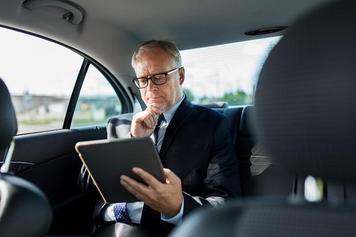 חוקים על שירות מענה ללקוחות: איש יושב במושב האחורי של מכונית ומסתכל על טאבלט
