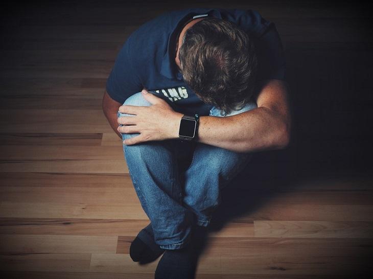 פעילות גופנית ונטילת תרופות: איש יושב על הרצפה עם ראש שפוף