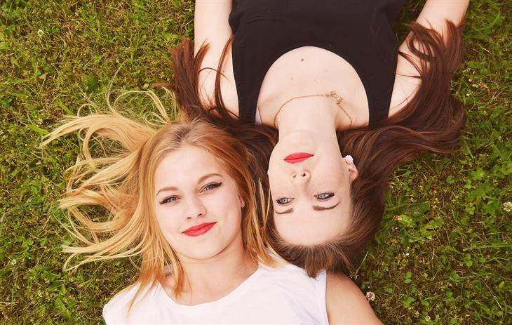 סיבות לאהוב את האויבים שלכם: שתי נערות שוכבות אחת לצד השנייה על הדשא