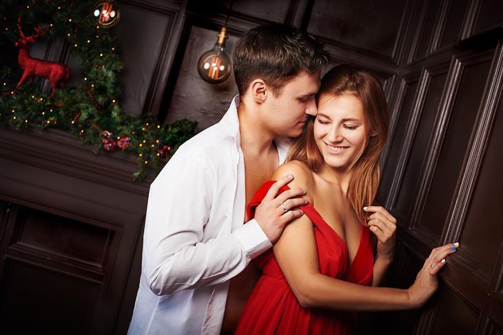 איך למנוע בגידה במערכת היחסים על פי המדע: גבר מחבק אישה ומתקרב כדי לנשק אותה