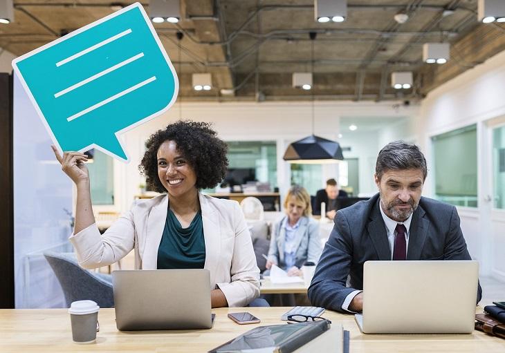 שירות לימוד שפות Mondly: אשה וגבר יושבים מול מחשבים, האישה מניפה שלט של בועית דיבור