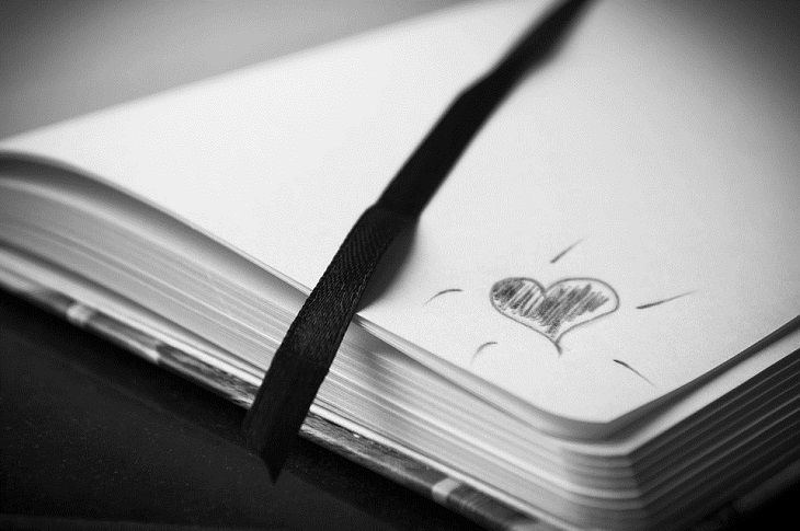 5 שפות האהבה: מחברת פתוחה עם סימן של לב בקצה הדף