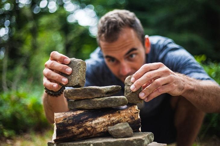 השגת מטרות: גבר מרכיב ערמת אבנים