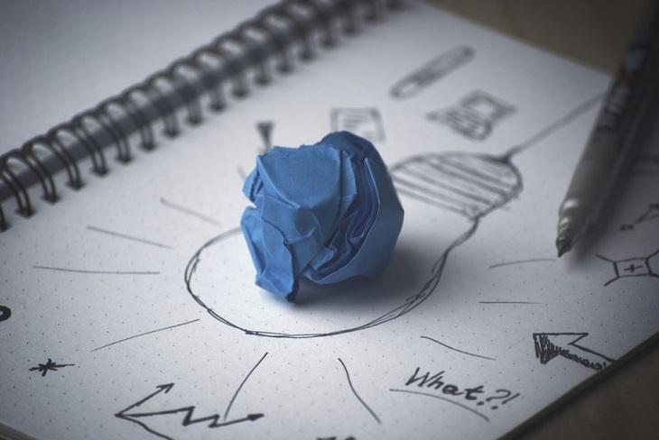 השגת מטרות: מחברת שעליה מצוירת מנורה ובתוכה דף מקומט