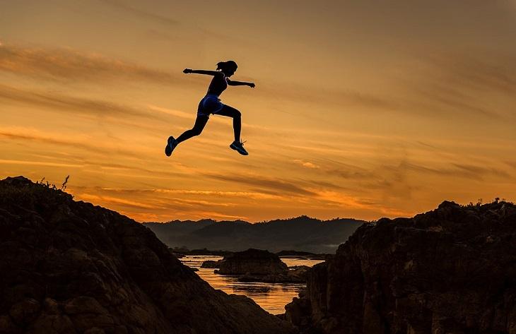 השגת מטרות: אישה קופצת בין שתי גבעות בשקיעה