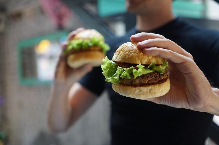 פחמימות מורכבות: גבר מחזיק שני המבורגרים