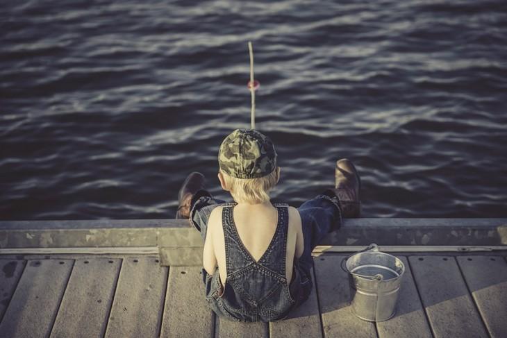 חינוך לאחריות ואושר: ילד יושב על רציף ודג עם חכה