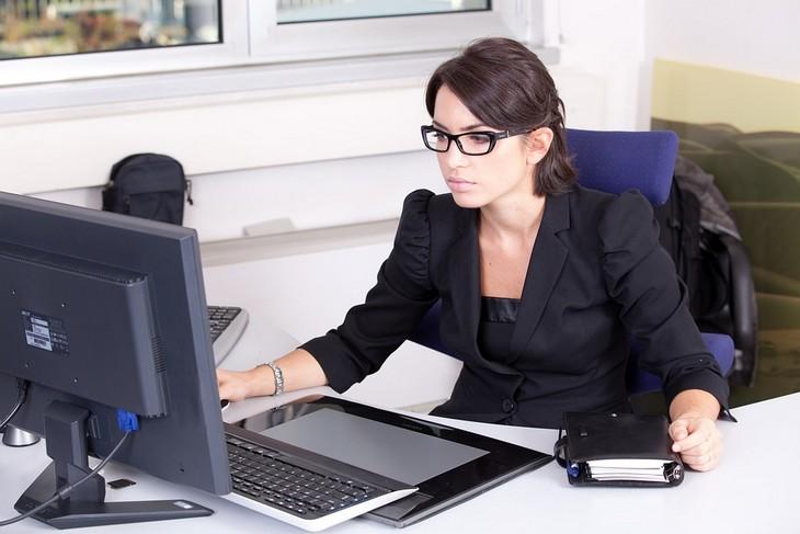 אופיס אונליין: אישה יושבת מול מחשב במשרד