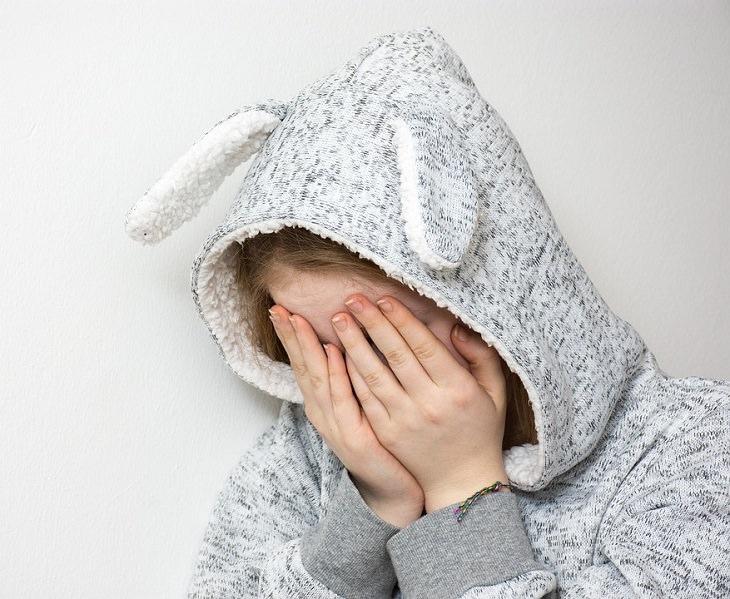טיפים להורים לילדים מתבגרים: נערה מסתירה את הפנים שלה