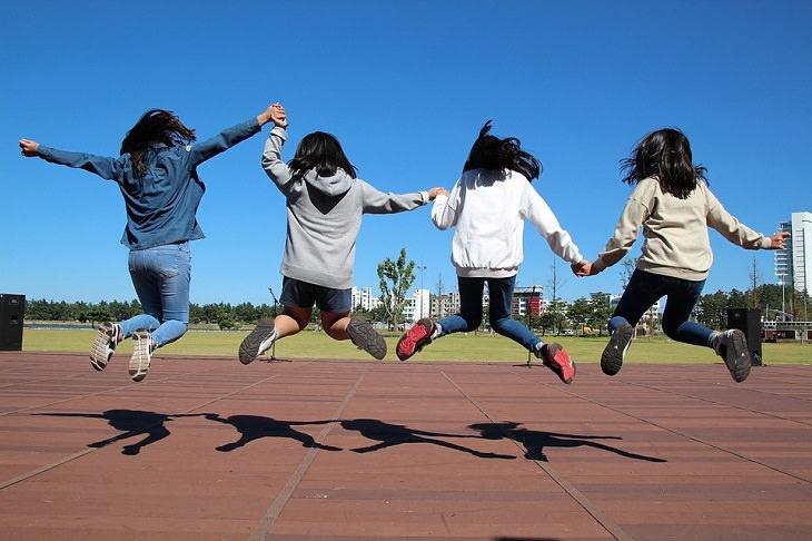 טיפים להורים לילדים מתבגרים: 4 נערות מחזיקות ידיים וקופצות באוויר