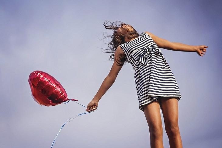הצלחה בחיים: אישה מחזיקה בלון עם ידיים פרוסות לצדדים