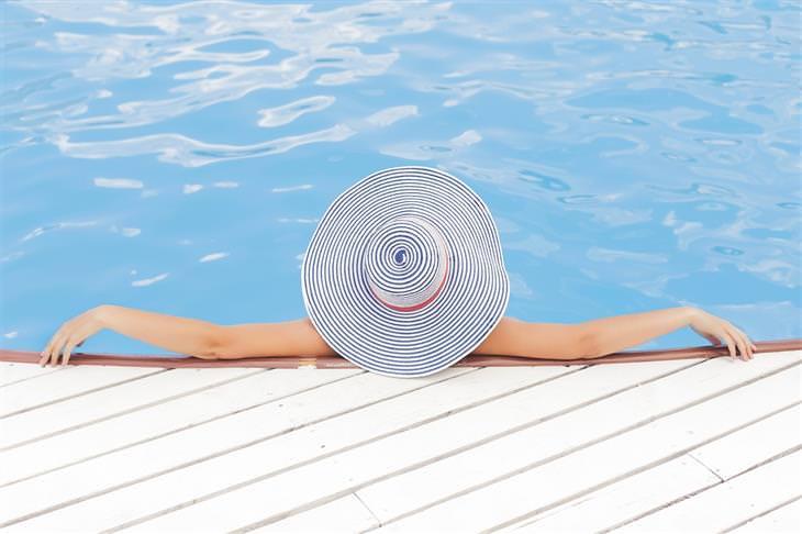 הסוד לחופשה המושלמת: אישה נשענת על מעקה בריכה וכובע שוליים לראשה