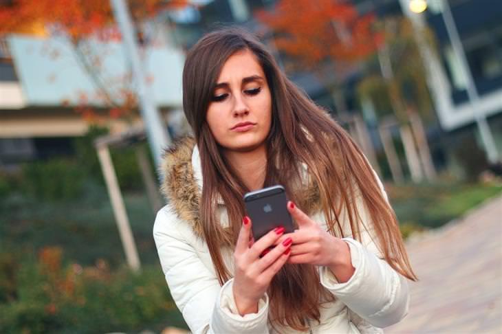 פתרונות טבעיים למניעת מחלת נסיעה: אישה מסתכלת על מסך סמארטפון