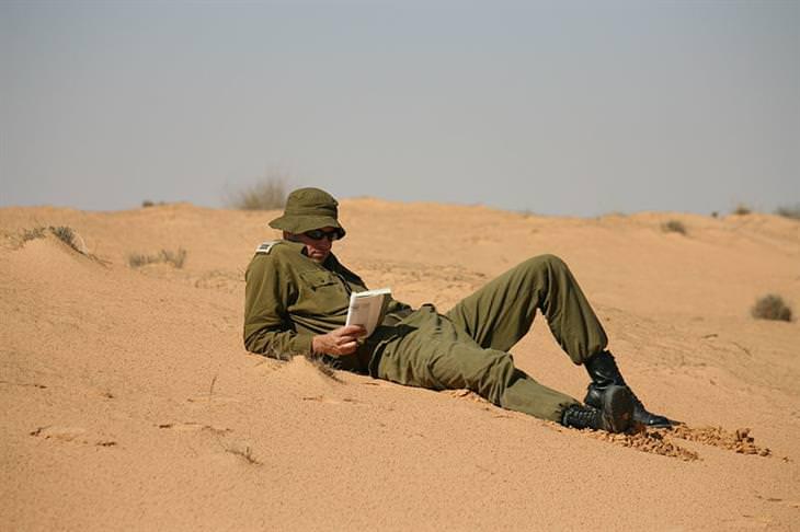 הסוד לחופשה המושלמת: קצין שוכב על חול מדבר וקורא ספר