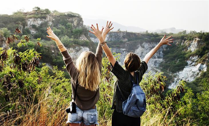 הסוד לחופשה המושלמת: שתי נשים מרימות את הידיים לאוויר מול נוף טבעי
