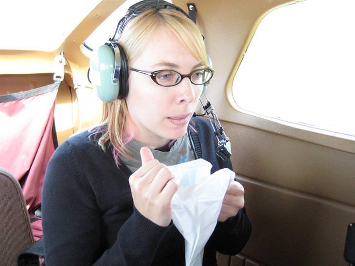 פתרונות טבעיים למניעת מחלת נסיעה: אישה יושבת במטוס עם אוזניות ומחזיקה שקית הקאה