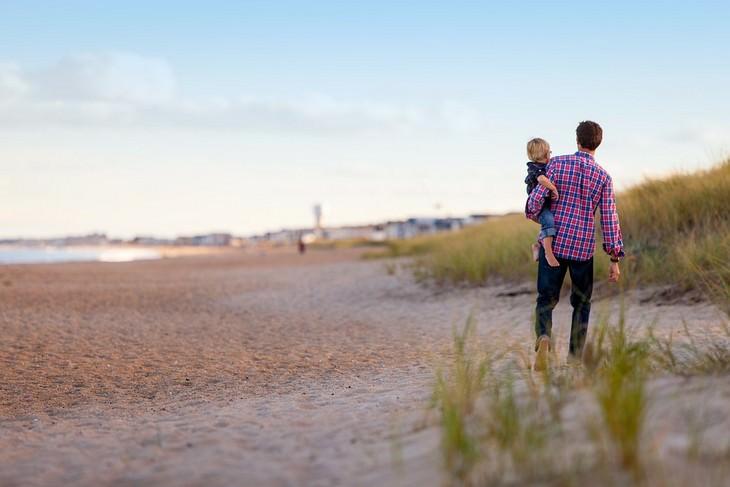 להיפטר מתירוצים: גבר מחזיק ילד על הידיים והולך איתו בחוף