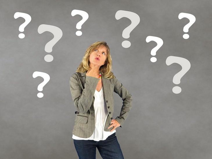 להיפטר מתירוצים: אישה עומדת וסימני שאלה מרחפים סביבה