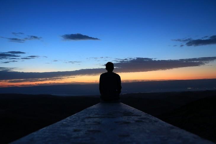להיפטר מתירוצים: גבר יושב על קצה של גג ומביט לשקיעה