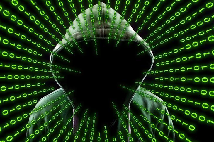 איך לזהות וירוסים במחשב ולהימנע מהם: איש שפניו מוסתרות תחת ברדס וסביבו ספרות 0 ו-1