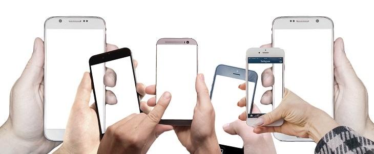 אפליקציות לניקוי הטלפון: ידיים אוחזות בטלפונים ניידים