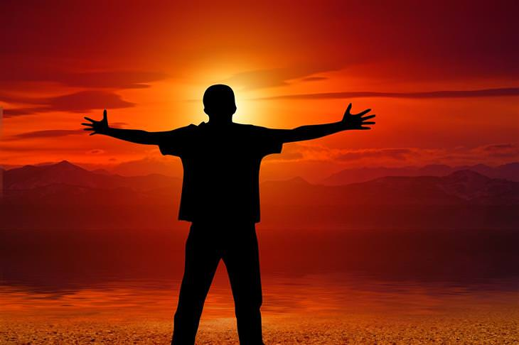 דברים שצריך לזכור בנוגע לדרך הקשה אל האושר: צללית של אדם עומד עם ידיים פרושות לצדדים מול שקיעה