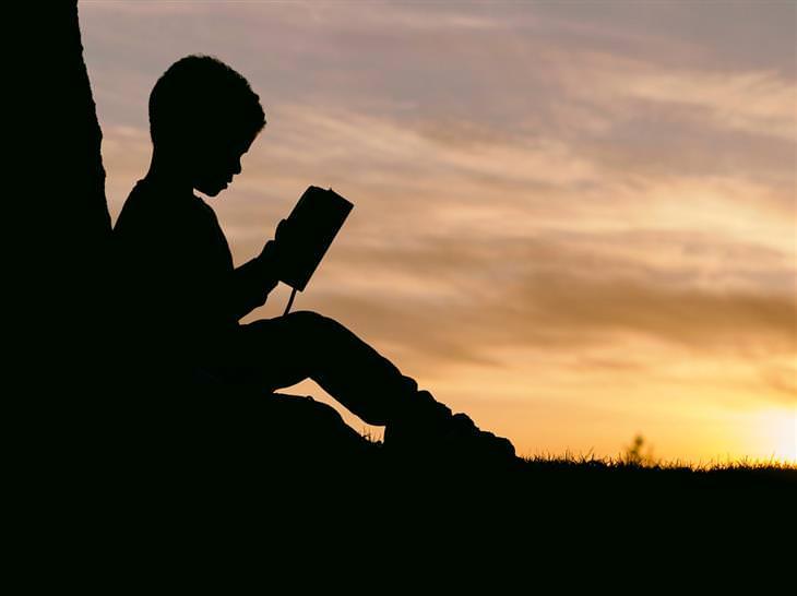 משל חיי נצח: צללית של ילד קורא ספר מול השקיעה