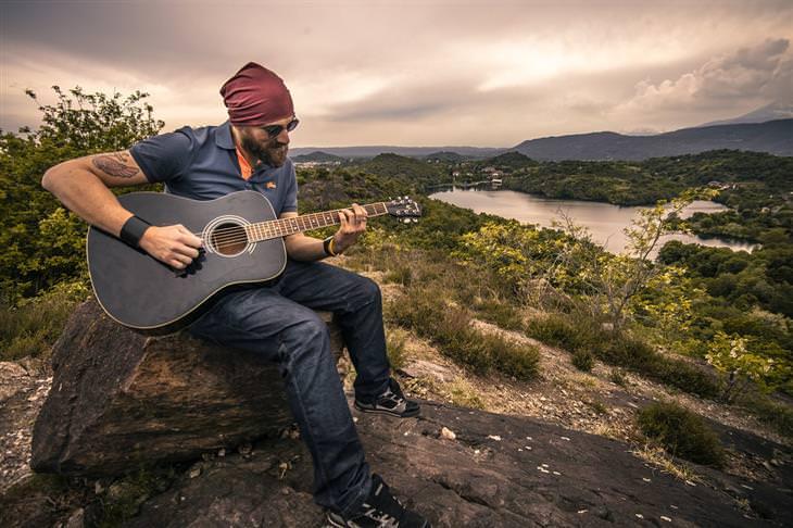 דברים שצריך לזכור בנוגע לדרך הקשה אל האושר: איש מנגן בגיטרה בטבע