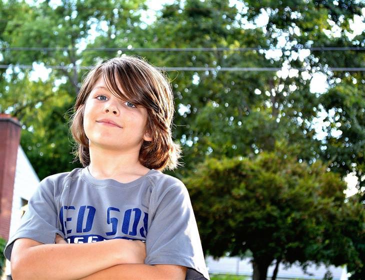 משל חיי נצח: ילד מסתכל למצלמה עם ידיים שלובות