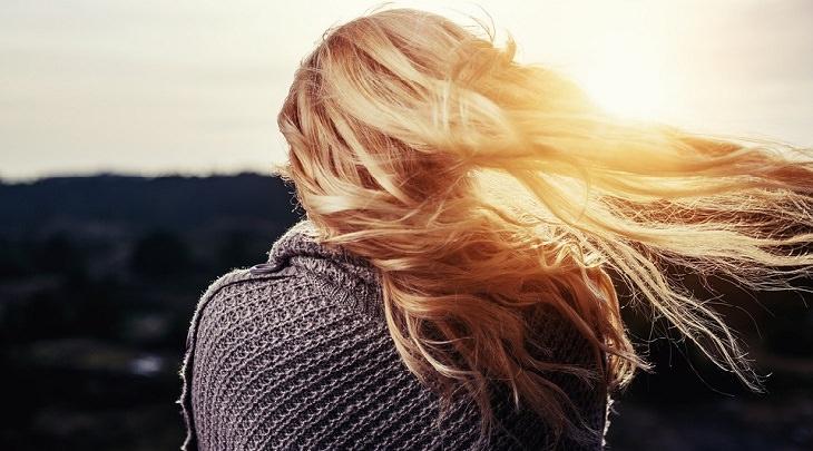 טיפול טבעי לצמיחת שיער: אישה עם שיער בריא על רקע השקיעה