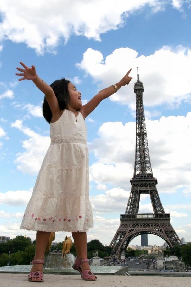 תמונות ברגע הנכון: ילדה מושיטה אצבע לראש מגדל אייפל