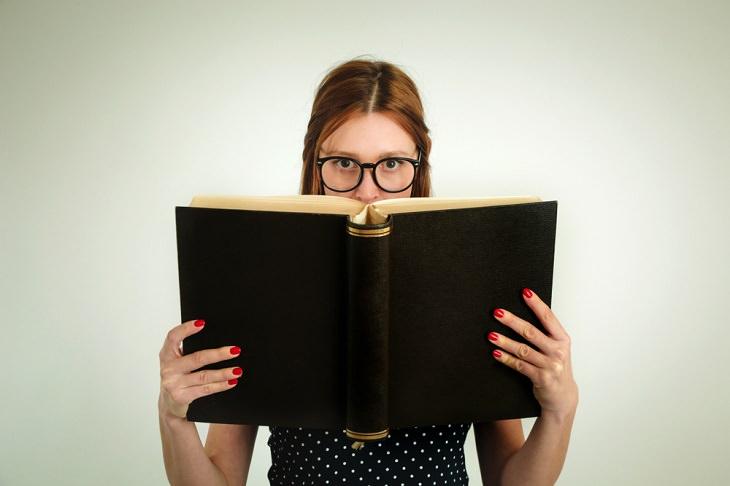 מילון מושגים למשכנתא: אישה עם משקפיים קוראת ספר