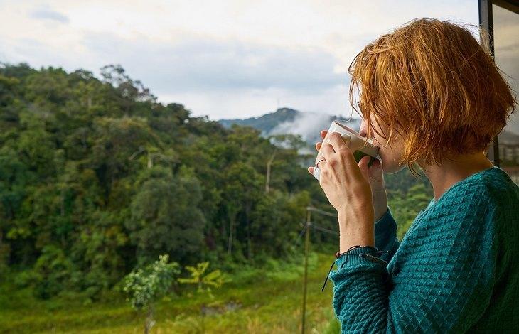 יתרונות השימוש בתוסף אסטזנטין: אישה שותה משקה על מרפסת ומשקיפה אל יער