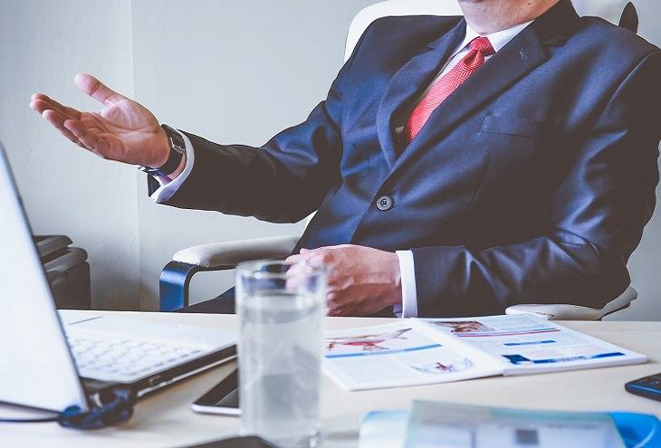 סגנונות ניהול: מנהל בחליפה יושב ליד שולחן