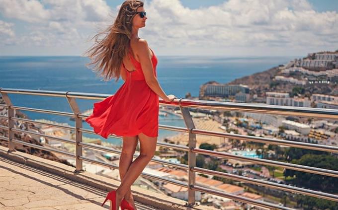 כמה אתה מוכן לחופשה: אישה עומדת במרפסת עם שמלה ועקבים ומביטה על הנוף