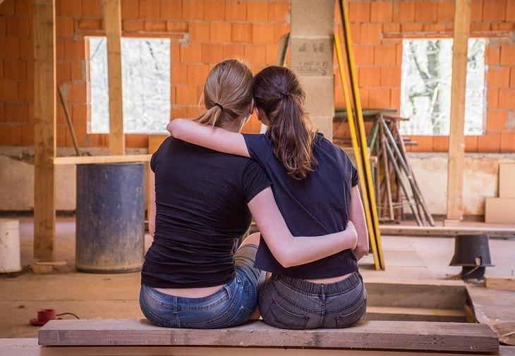 משפטים שיגרמו לאנשים לחבב אתכם: שתי נשים יושבות ומתחבקות