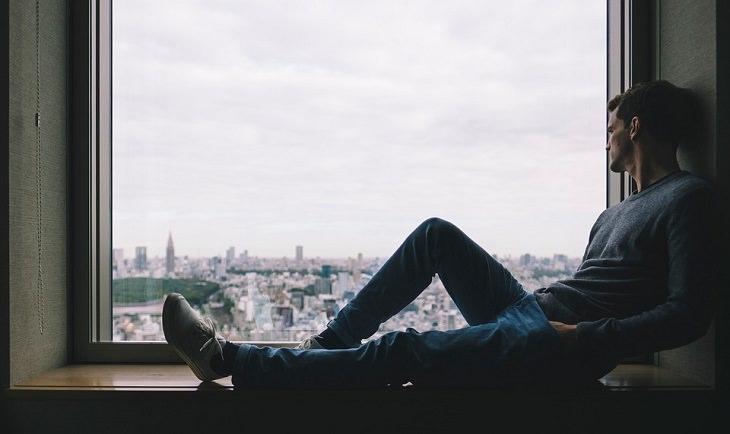 משפטים שיגרמו לאנשים לחבב אתכם: גבר יושב על אדן החלון ומביט החוצה