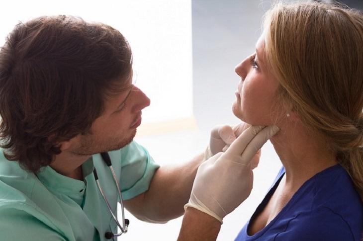 זיהוי בעיות בתפקוד בלוטת התריס: רופא בודק לאישה את בלוטת התריס